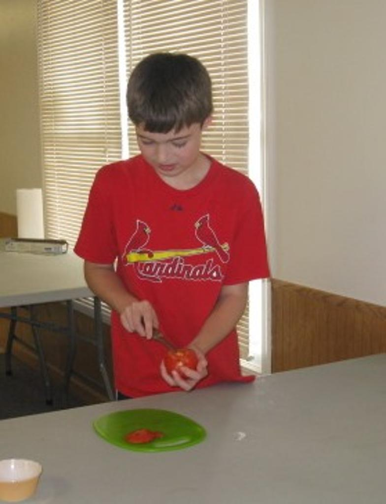 Asher chops tomato for tacos on Mexican Day