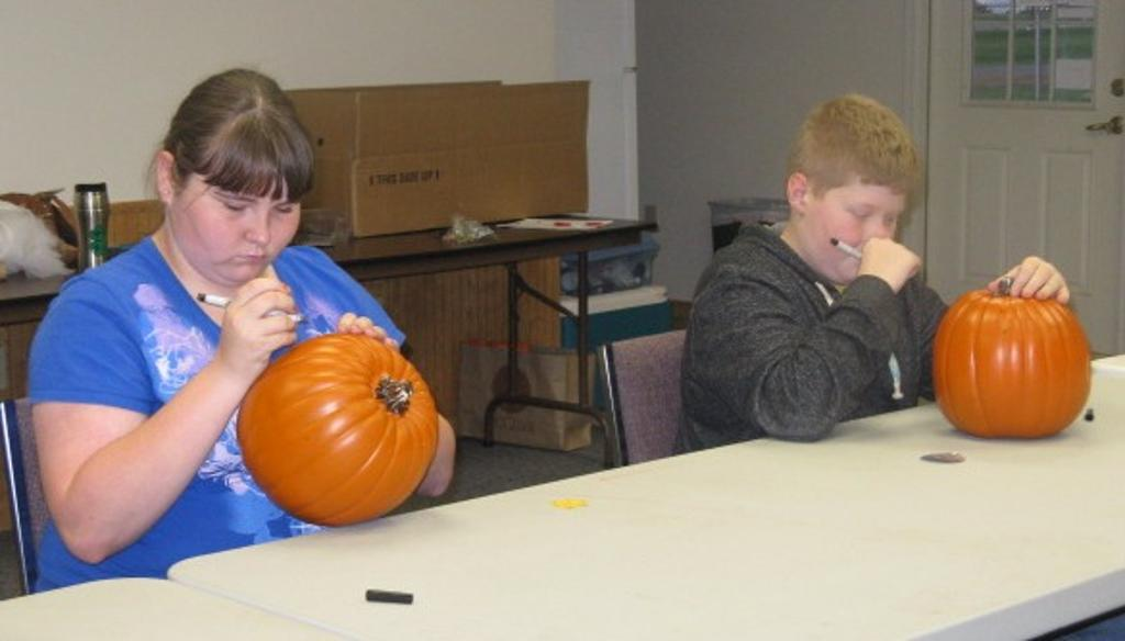 Ashley and Roux make designs on their pumpkins.