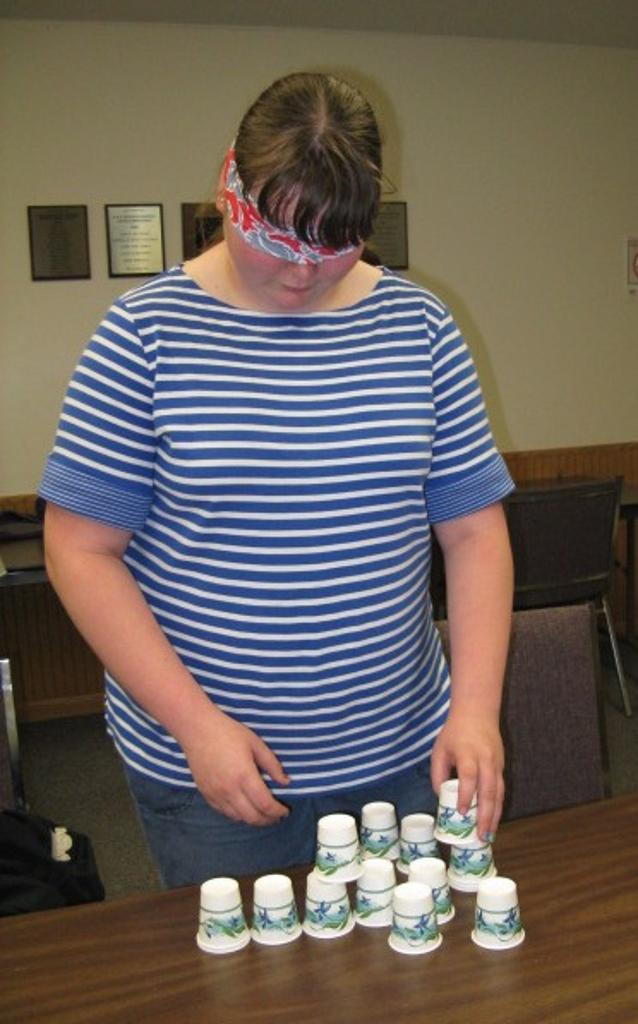 Ashley depending on her 'leader' to guide her in creating a tower of cups.