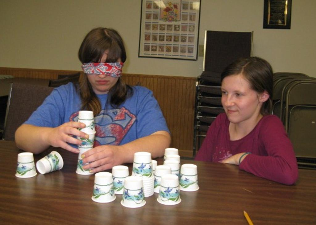 "Sarah leading ""blind"" Hannah in creating a stack of cups."