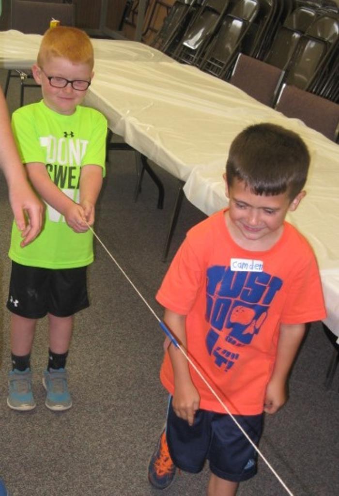 Kamdin and Camden work with their balloon rocket.