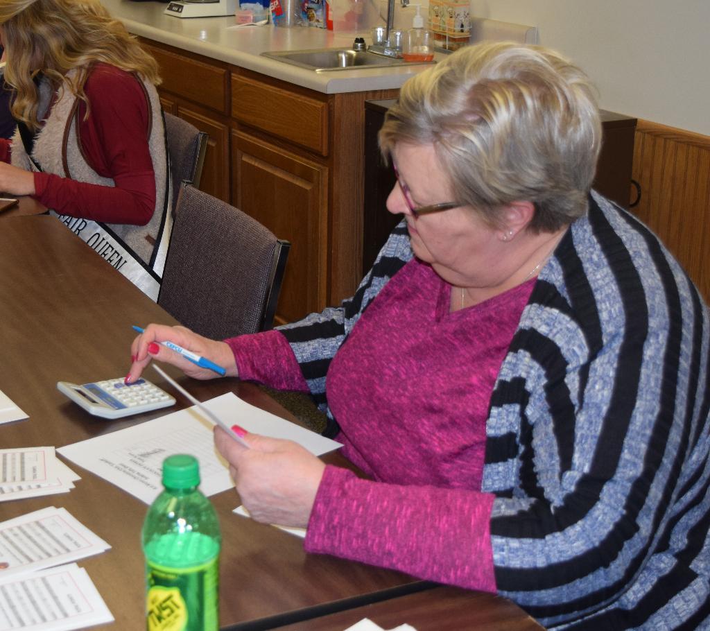 Carol helps tally judging scorecards
