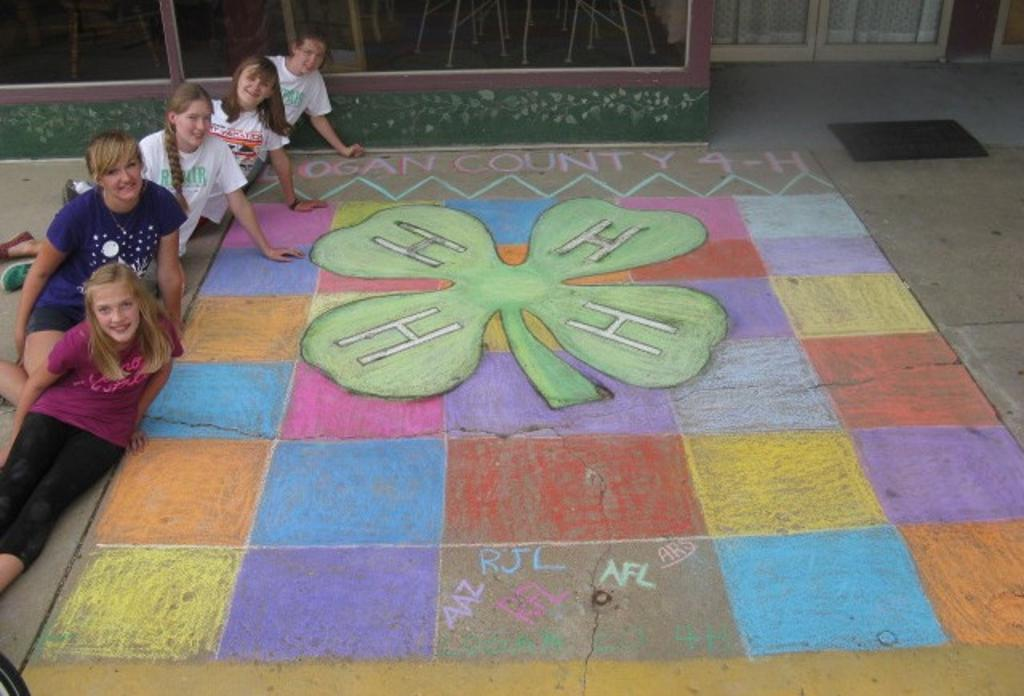 Abi, Ashley, Raelyn, Alyssa, and Ruth pose next to the completed 4-H Chalk Art square!