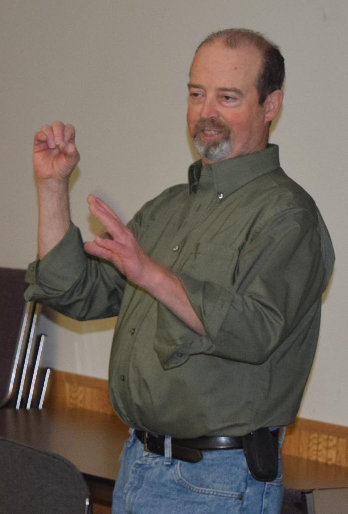 Instructor, Chuck Gunning, demonstrates the sign language alphabet
