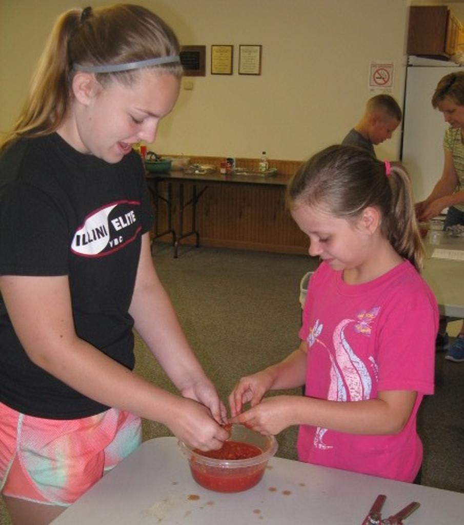 Claire and Emma crush tomatoes for marinara sauce on Italian Day