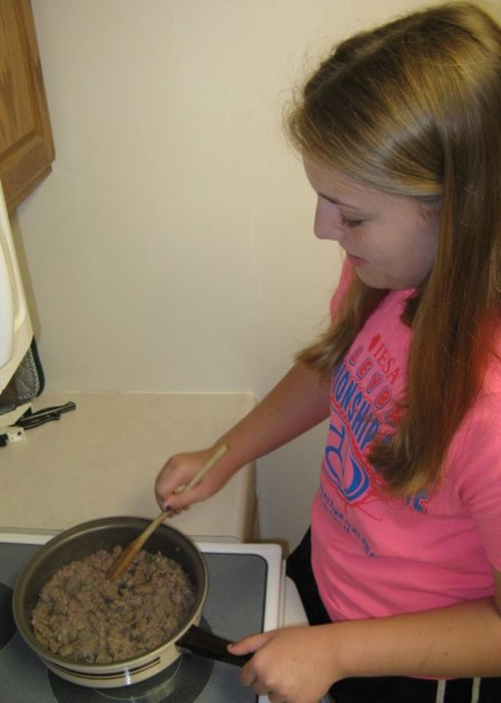 Claire cooks sausage for egg rolls on Japanese Day