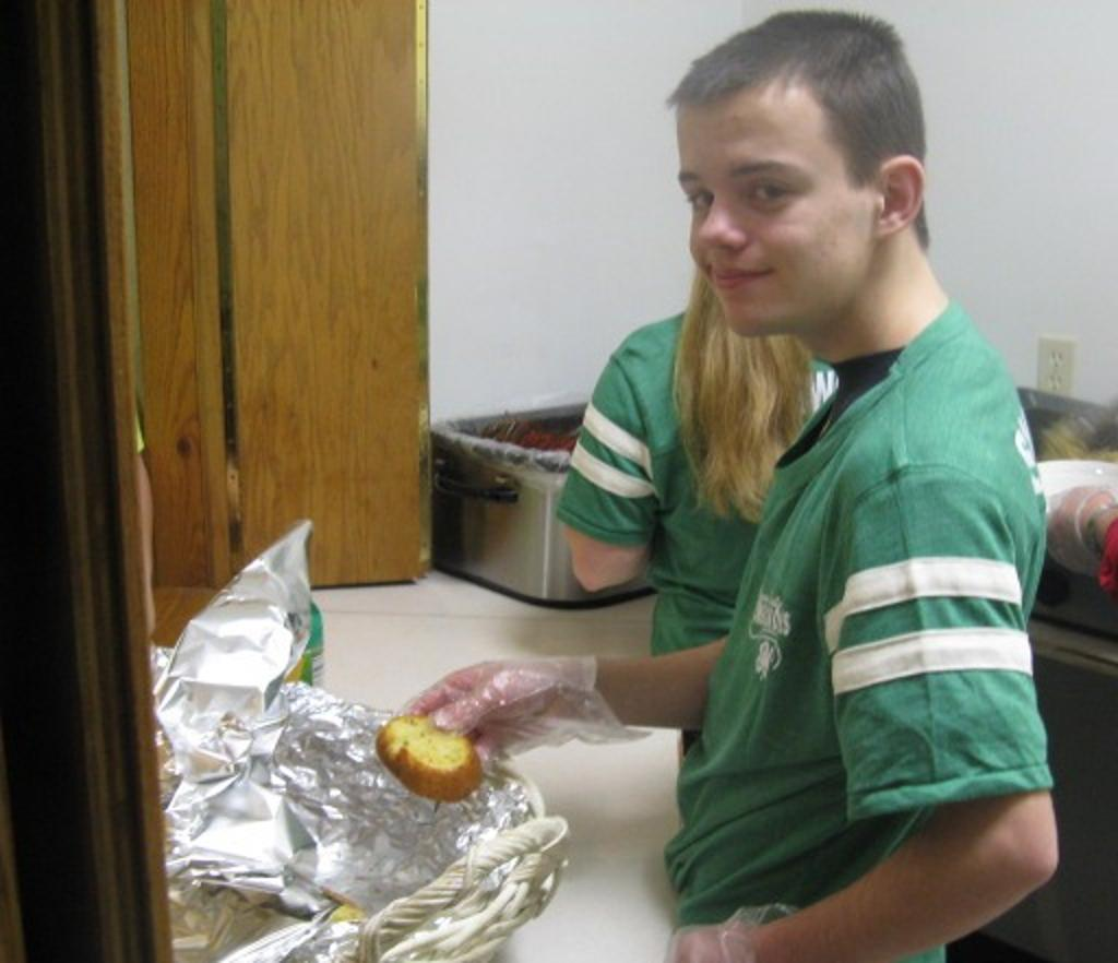 4-H Ambassador Clayton assists with serving the meal