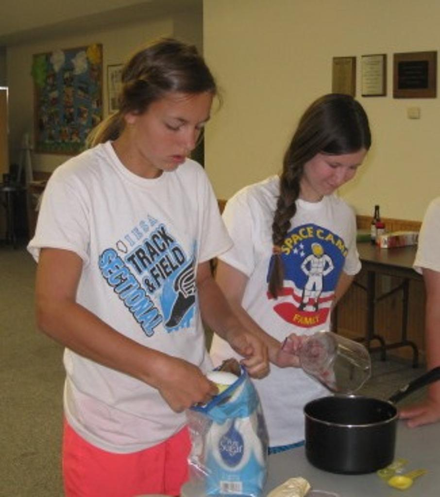 Diane and Sarah measure ingredients for churro dough on Mexican Day