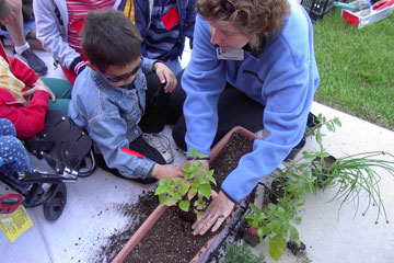 Master Gardener teaches child about plants