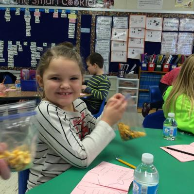 A student from Auburn's 1st Grade class samples her pig