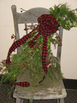 Swag made from cedar, pine, boxwood, bittersweet, decorated with a bow on an old chair.