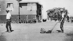 StateLibQld 1 107288 Groundsmen mowing the lawn on a tennis court at Clayfield  ca  1925  1