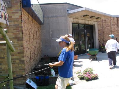 Nancy Kreith pulling hose for watering beds