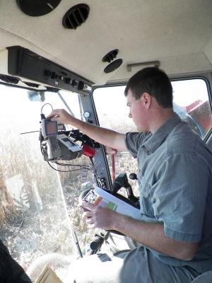 Figure. Brian Mansfield, NWIARDC Research Agronomist,  programming the combine computer to collect yield,  moisture, and test weight data.