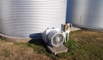 Figure. An aeration fan attached to a grain bin. This fan dries grain very slowly as it pulls in air at ambient temperatures and moistures.